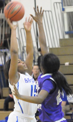 Jayla Anderson (15) reaches high to get a shot away. (Photo by Kevin Nagle)