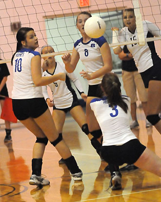Nikki Clay (3) digs up a hit behind Rylee Phillips (10) and Brittney Sahlmann. (Photo by Kevin Nagle)