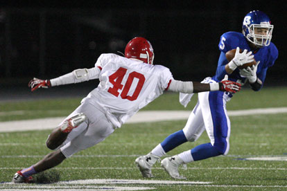 Sophomore Austin Kelly (5) makes a catch and cuts back past McClellan's Miguel Evans (40). (Photo by Rick Nation)