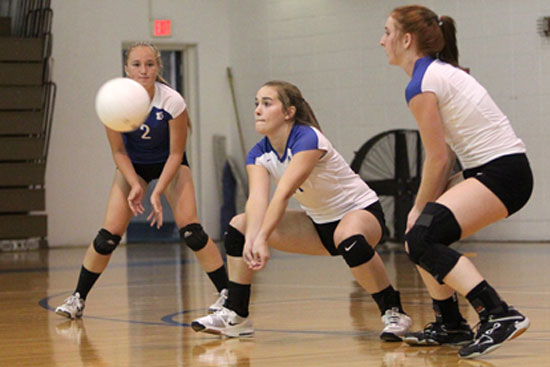 Abby Staton digs up a hit, flanked by Whitney Brown (2) and Nikki Clay (3). (Photo by Rick Nation)