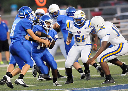Diante Woodson (11) takes a handoff from Michael Jones (8) as North Little Rock defenders Deontray Ross (51) and Ficklin Khai (19) converge. (Photo by Kevin Nagle)