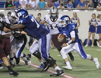Gunnar Burks (3) looks for room to run off of the block of Cameron Davis (77). (Photo by Rick Nation)