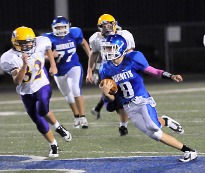 Quarterback Michael Jones (8) looks for running room after getting a block from Josh Wyllia (77). (Photo by Kevin Nagle)