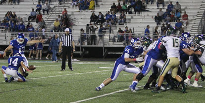 Alex Denker kicks one of his three field goals out of the hold by Madison Schrader. (Photo by Rick Nation)