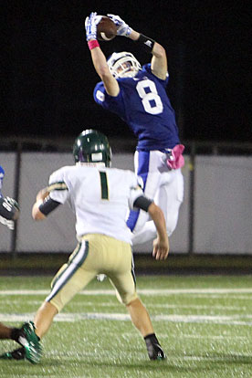 Aaron Orender (8) goes high to grab a pass over Alma's Heath Friddle (1). (Photo by Rick Nation)