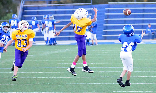 Tristan Hays (26) prepares to catch a pass over a pair of Horace Mann defenders. (Photo by Kevin Nagle)