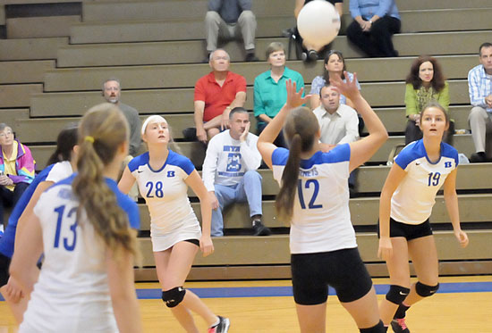 Sarah Kennedy (12) sets the ball for teammate Shaelyn Smith (19) as Reagan Blend (28) gets in position. (Photo by Kevin Nagle)