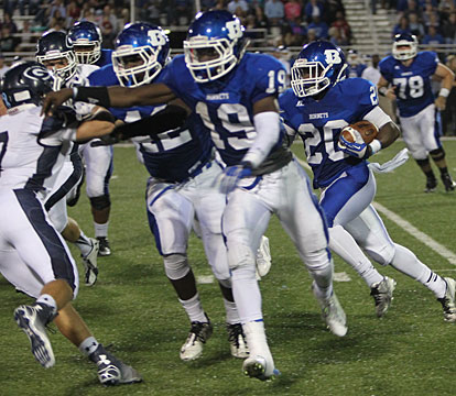 Kylon Boyle (19) and Demaja Price lead DeAmonte Turner around the corner. (Photo by Rick Nation)