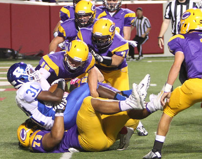 Sevante Turner (31) falls into the end zone in the arms of Catholic's Luc Bequette. (Photo by Rick Nation)