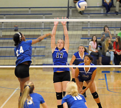 Tori Allen (17) attempts a block as Raven Loveless (24, to right), and Ashlyn Lee (25) position themselves for a dig. (Photo by Kevin Nagle)