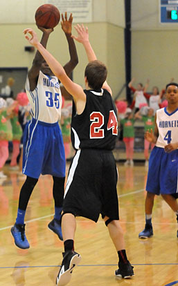 Randy Thomas (35) fires a 3-pointer over Russellville's Bryson Kordsmeier during Monday's game. Josh Robertson is number 4. (Photo by Kevin Nagle)