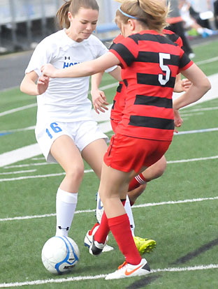 Jessica Butler (16) battles a Cabot player for possession. (Photo by Kevin Nagle)