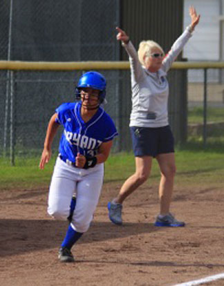 Mallory Theel rounds third and heads for home as head coach Debbie Clark directs the runners behind her. (Photo courtesy of Jon Staton)