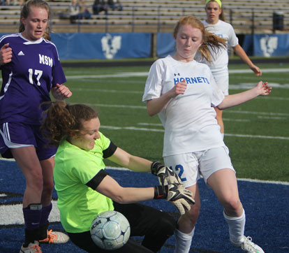 Caroline Campbell (12) fights to get a shot past the Mount St. Mary goalkeeper. (Photo by Rick Nation)