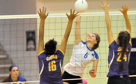 Allie Anderson goes high on a hit during her 21-kill performance Tuesday night. Teammate Shayla McKissock, left, gets ready for a return. (Photo by Kevin Nagle)