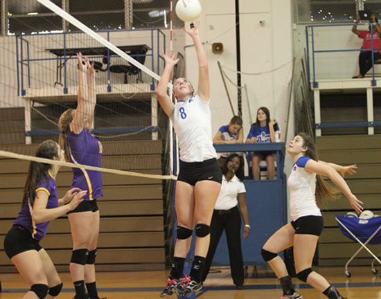 Britney Sahlmann (8) goes high for a tip during Tuesday's season-opening win. (Photo by Rick Nation)