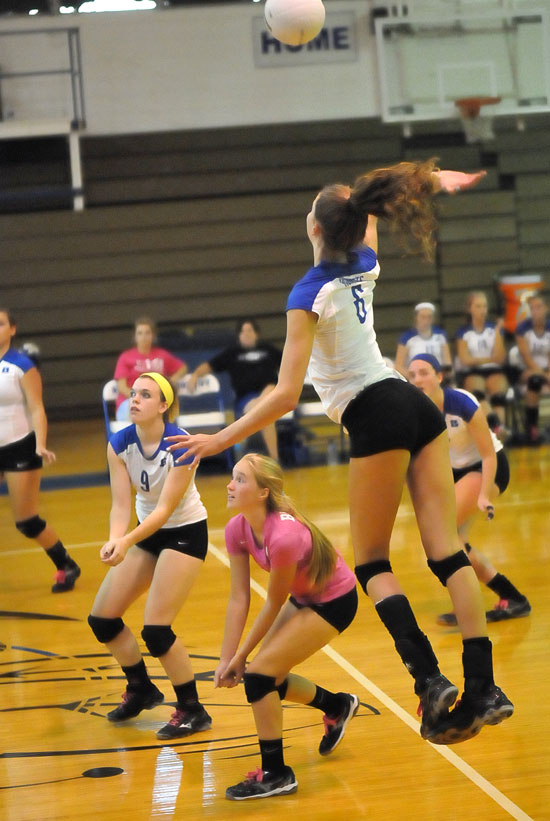 Allie Anderson leaps high for a hit as teammates Kendall Selig, Whitney Brown and Britney Sahlmann get into position. (Photo by Kevin Nagle)
