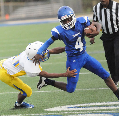 Christian Cain (4) tries to avoid a Lakewood tackler. (Photo by Kevin Nagle)