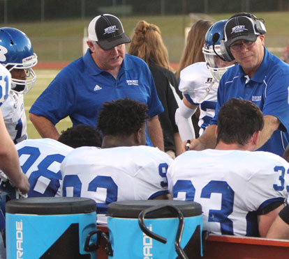 Coaches Brad Stroud, left, and Steve Griffith talk to the defense on the Bryant bench. (Photo by Rick Nation)
