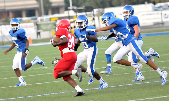 Hornets defenders pursue McClellan running back Deairrrus Montgomery. (Photo by Kevin Nagle)