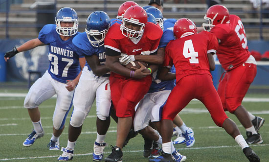 Jakob Neel (37) joins a pair of his teammates as they try to make a tackle. (Photo by Rick Nation)