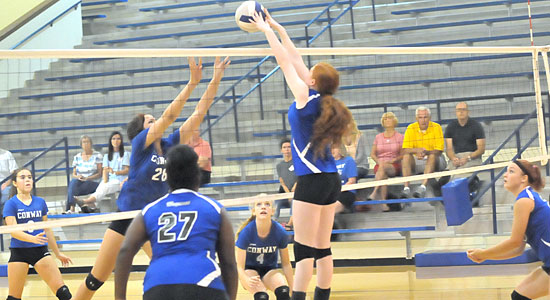 Faith Stone goes high to make a block. (Photo by Kevin Nagle)
