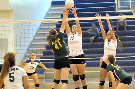 Brittney Warner (16) and Shaelyn Smith (7) go up for a block in front of teammate Ashlyn Lee (25). (Photo by Kevin Nagle)