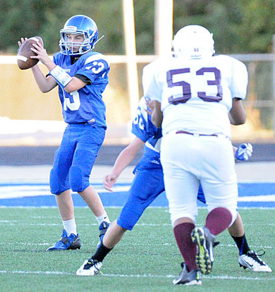 Jagger Littleton takes a snap as teammate Jacob Shelby (60) protects. (Photo by Kevin Nagle)