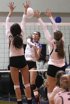 Allie Anderson splits a pair of Conway blockers with a spike. (Photo by Rick Nation)
