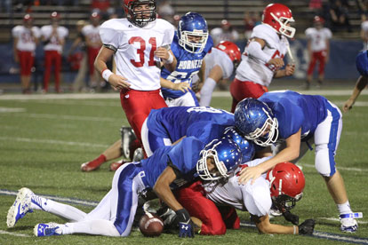 The ball comes loose as a trio of Hornets tackle Cabot Red running back Bradley Morales. (Photo by Rick Nation)