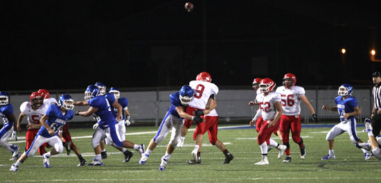 Cabot Red quarterback Cameron Thames (9) gets drilled after releasing a pass. (Photo by Rick Nation)