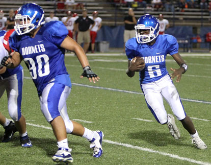 Quarterback Randy Thomas (6) follows guard Josh Salguerio (90) around left end. (Photo by Rick Nation)