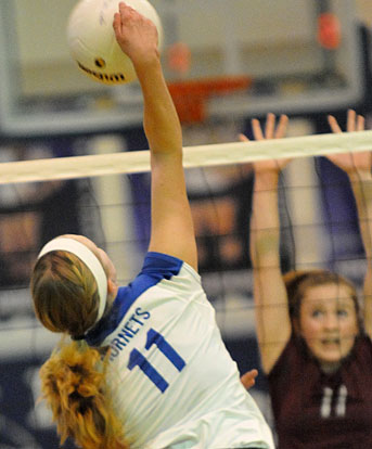 Reagan Blend reaches above the net on a spike. (Photo by Kevin Nagle)