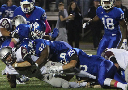 Hayden Knowles, Mario Waits and Devon Alpe bring down Siloam Springs quarterback Jordan Norberg. (Photo by Rick Nation)
