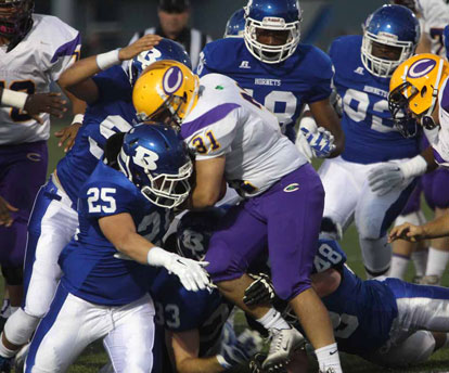 Devon Alpe and his defensive cohorts stack up Catholic running back Austin Berry (31). (Photo by Rick Nation)
