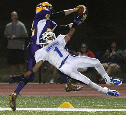 Catholic's Will Plafcan battles Bryant's Andrew Hayes (1) for a pass. (Photo by Rick Nation)
