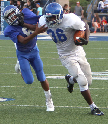 Bryant White running back Myles Aldridge stiff arms a Bryant Blue defender. (Photo by Rick Nation)