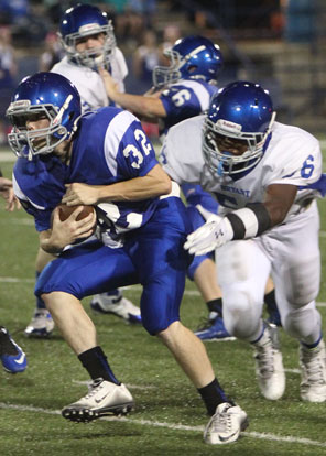 Bryant White's Austin Bailey (56) tries to bring down Bryant Blue runner Dalen McDonald (32). (Photo by Rick Nation)