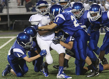 Bryant White quarterback Derrick Rose is swarmed under by Bryant Blue's Ryan Riedmueller (15), Hayden Holt (21) and their teammates. (Photo by Rick Nation)