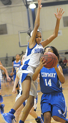 Jada Deaton (4) goes up for a block. (Photo by Kevin Nagle)