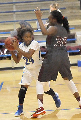 Kalia Walker (24) looks for room around Benton's Tamia Halk. (Photo by Kevin Nagle)