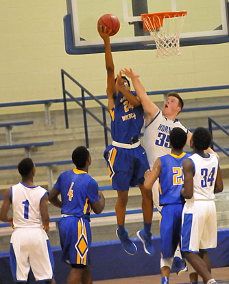 Blaise Smith (35) tries to block a shot as teammates Randy Thomas (34) and Daelin Drake (1) looks on. (Photo by Kevin Nagle)