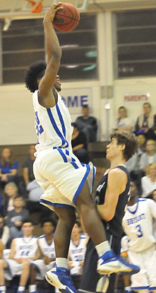 Greenwood's Dustin Lunsford takes a charge as Bryant's Lowell Washington eyes a potential dunk. (Photo by Kevin Nagle)