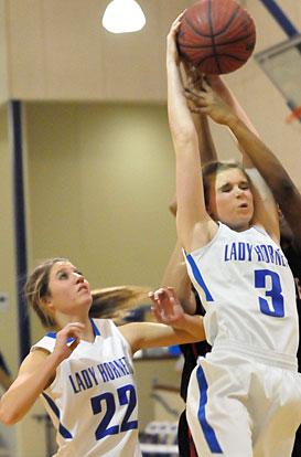 Rachel Studdard (3) pulls down a key rebound as teammate Lauren Burnett arrives to help. (Photo by Kevin Nagle)