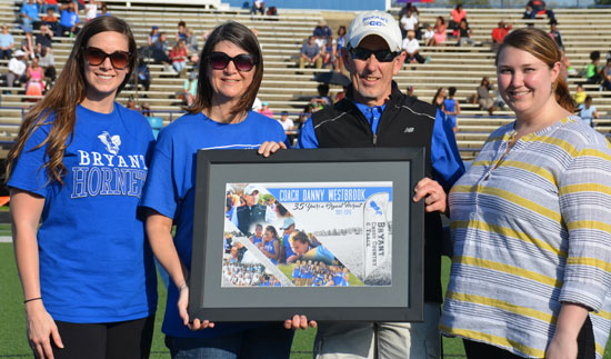 Lady Hornets head coach Danny Westbrook was presented a plaque commemorating his 35 years as a coach at Bryant. He is flanked by his wife Vicki and daughters