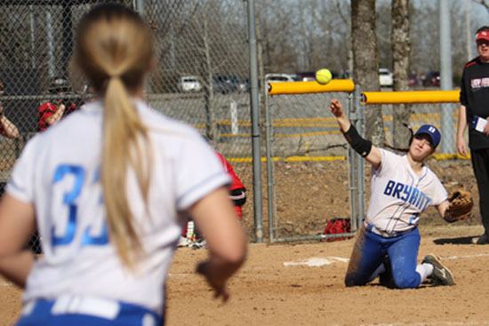 Shayla McKissock throws to Mallory Theel (33) at first from her knees after making a diving stop at third. (Photo by Rick Nation)