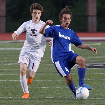 Bryant's Connor Qualls (4) dribbles ahead of Benton's Tyler Sandiver (1). (Photo by Rick Nation)