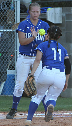 Mallory Theel takes a throw at first base from teammate Macey Jaramillo. (Photo by Rick Nation)