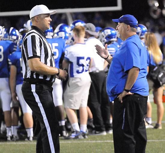 Bryant head coach Buck James talks to the official about a call that went against the Hornets. (Photo by Kevin Nagle)