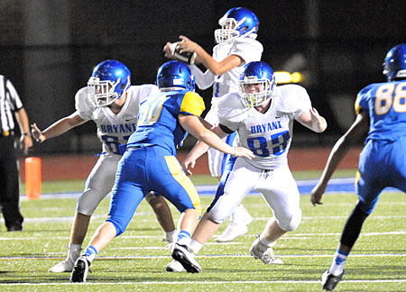 Quarterback Jake Meaders controls a high snap in the background as Brantley Thomas (67) and Tanner Wilson (83) provide protection. (Photo by Kevin Nagle)